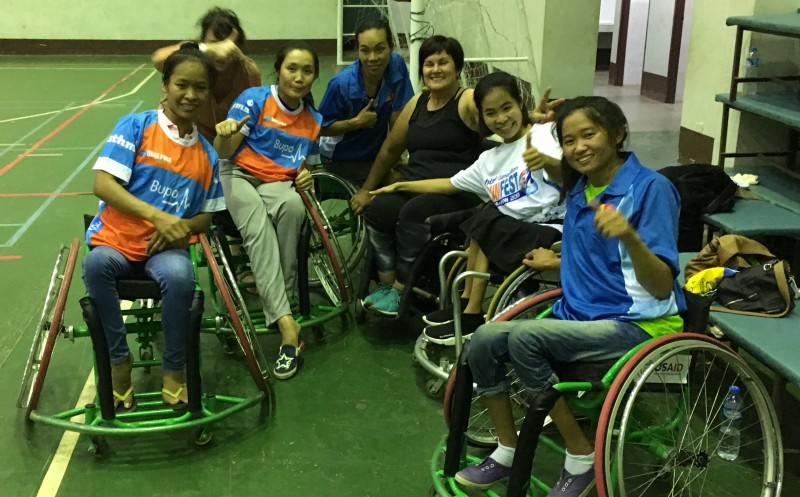 Chris Kerr with local Laos women at wheelchair basketball training.